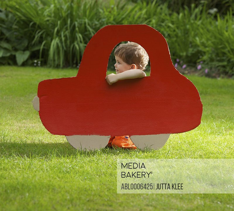 Young Boy Kneeling behind Cardboard Cut Out in Shape of Car