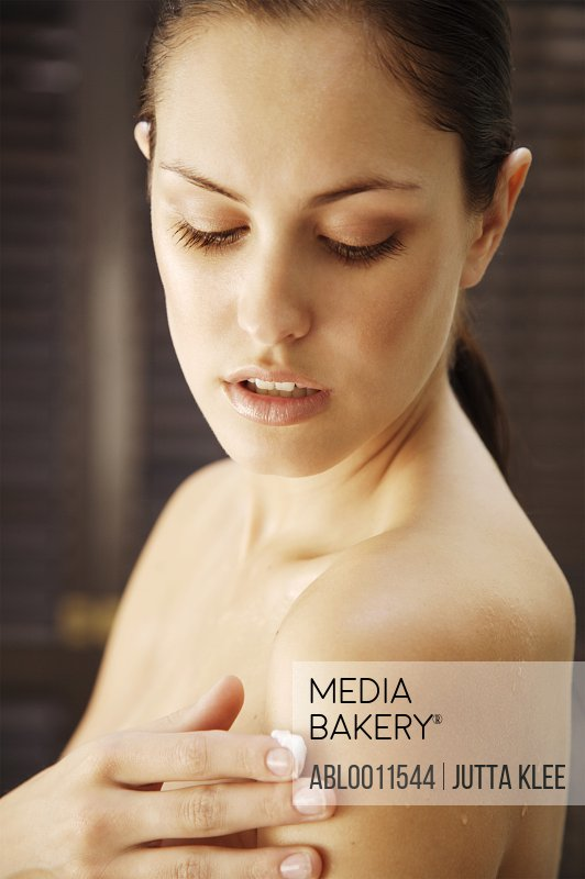 Portrait of a woman applying body lotion on shoulder
