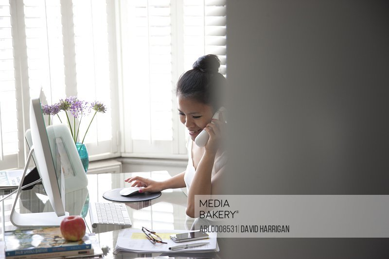 Woman Working at Desk Using Telephone