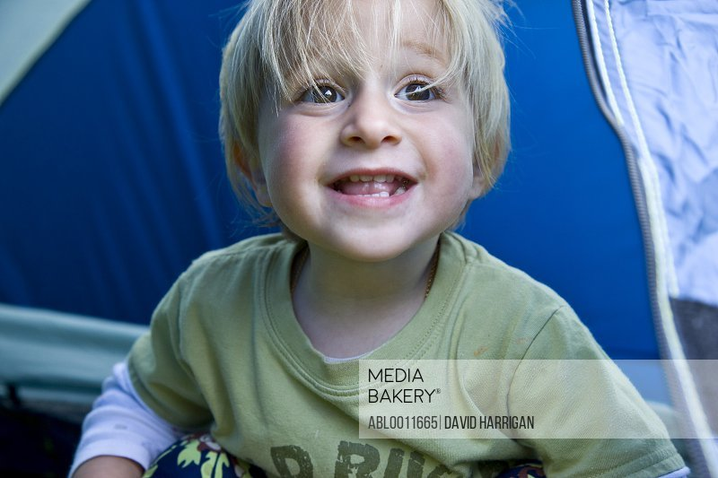 Young blonde boy playing inside a tent
