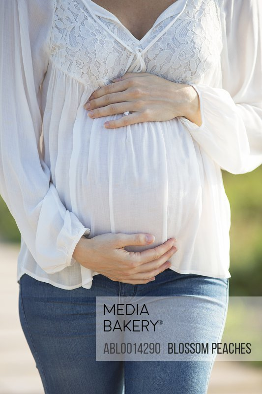 Pregnant Woman Holding her Stomach, Cropped view
