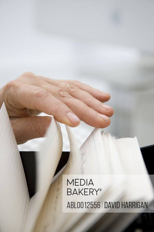 Close up of a woman hand flicking through contact cards