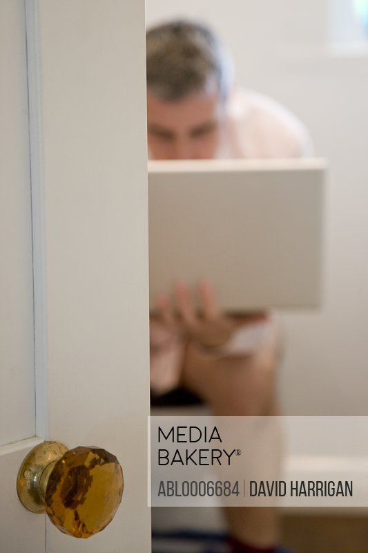 Man Sitting on Toilet Using Laptop