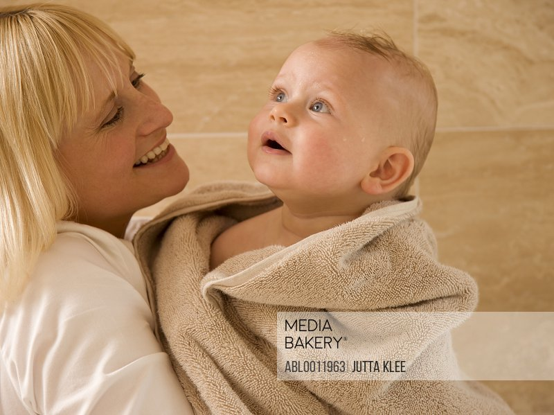 Close up of baby wrapped in  a towel with his mother holding him