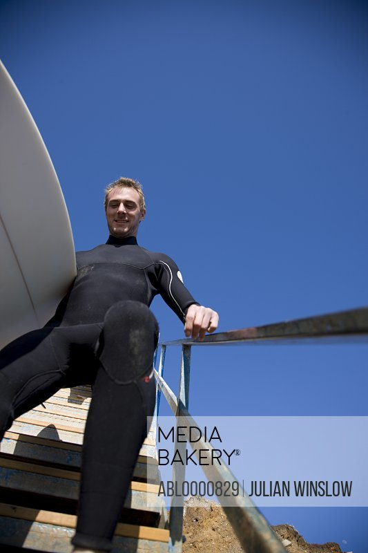 Young surfer descending a staircase holding surfboard