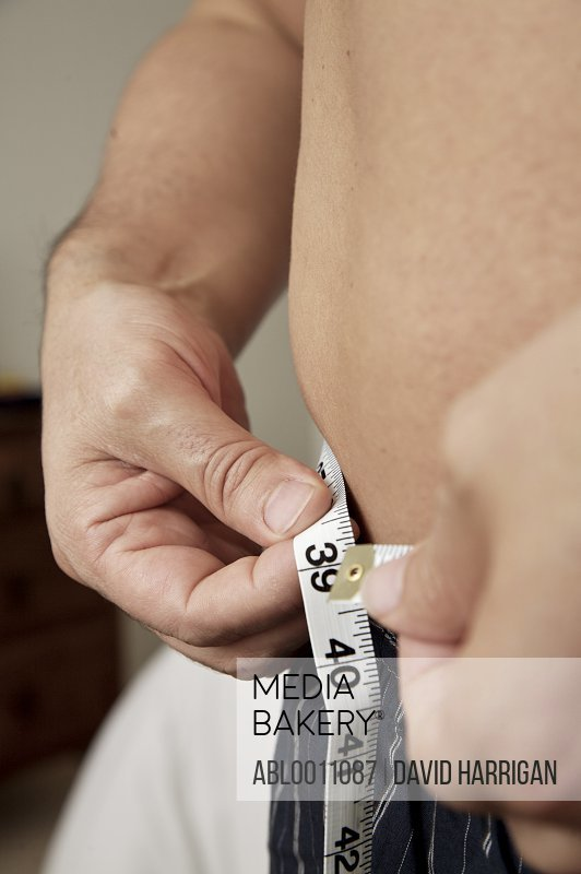 Close up of man measuring waist with tape measure