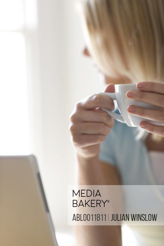 Woman Drinking Coffee opposite Laptop