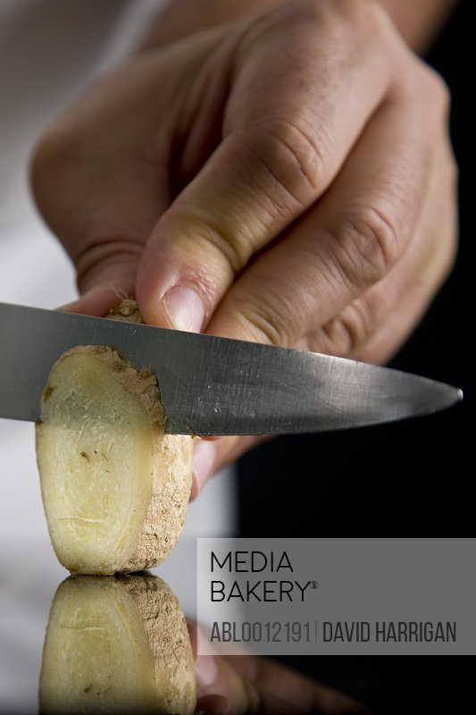 Close up of a chef hand slicing ginger