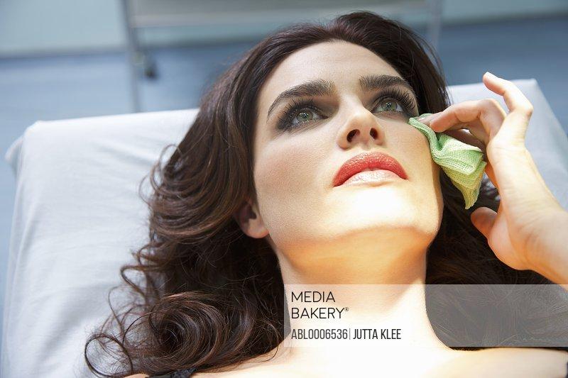 Woman's Wiping Corner of Eye with Green Gauze