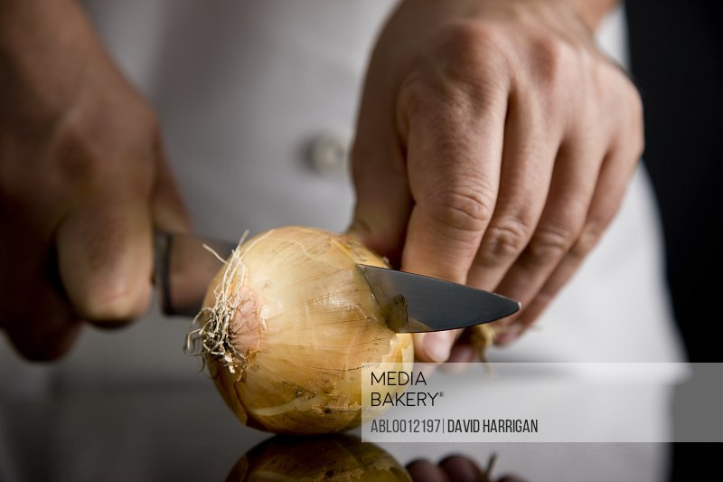 Close up of a chef hands cutting an onion