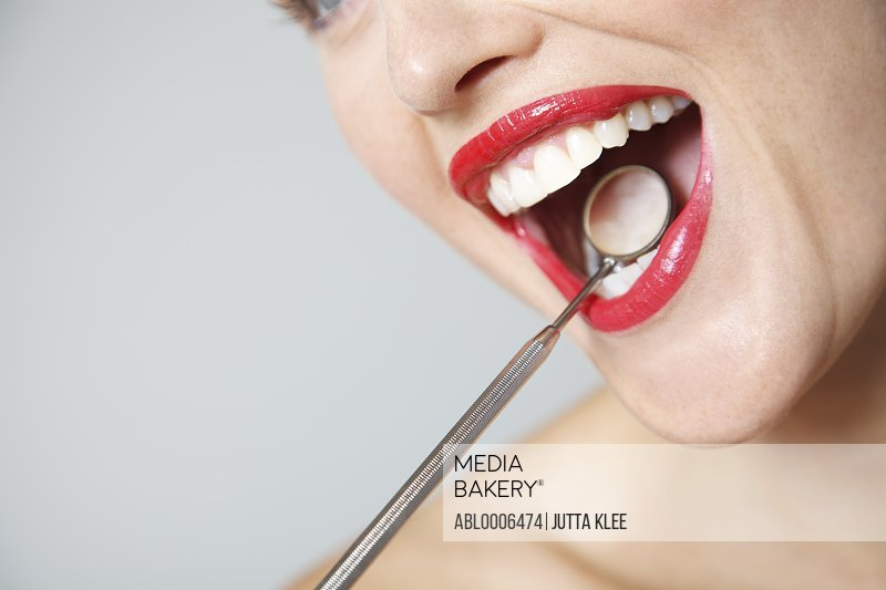 Close up of Woman's Mouth with Red Lipstick during Dental Examination