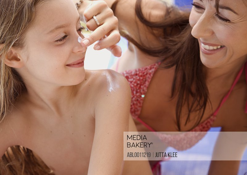 Mother applying sunscreen lotion on daughter nose