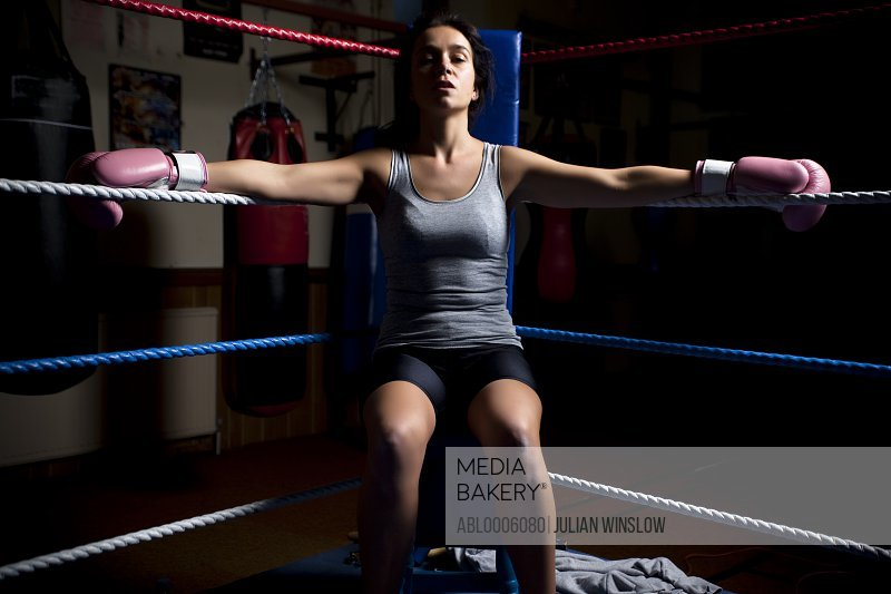 Woman sitting in a corner of boxing ring