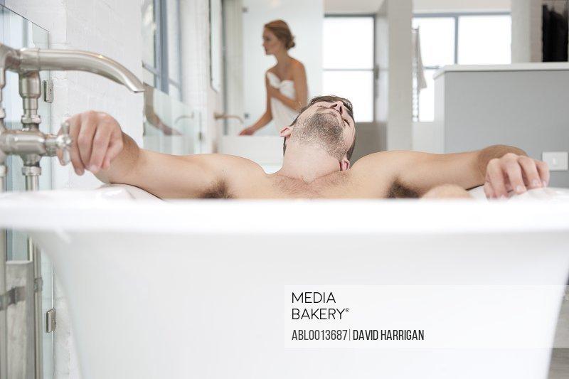 Man Relaxing in Bathtub, Woman in Background