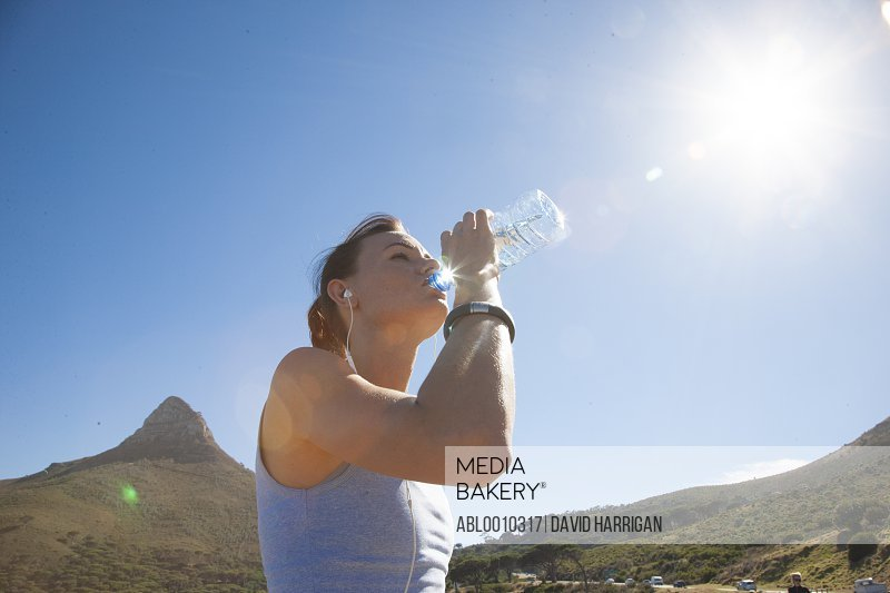 Woman Drinking Water from Bottle, Lion's Head Mountain in background, Cape Peninsula, South Africa