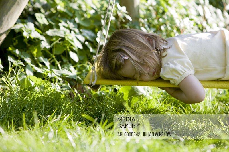 Young girl lying on a swing sleeping