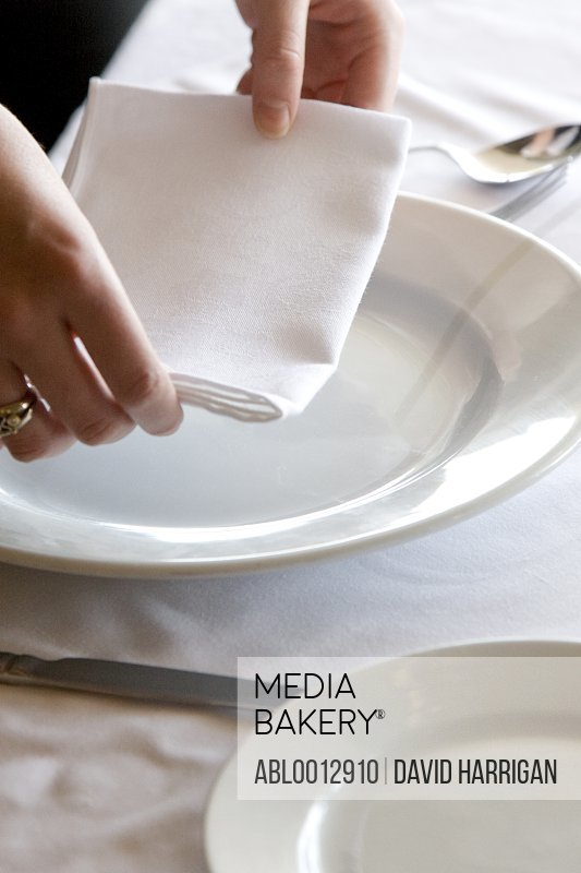 Close up of a waitress's hands arranging a napkin on a restaurant table