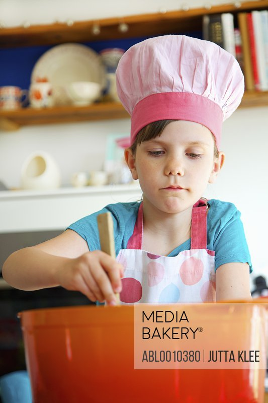 Young Girl Wearing Chef's Hat Stirring Casserole