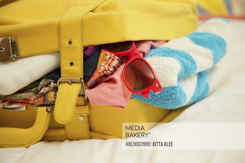 Yellow Suitcase Bursting with Clothing