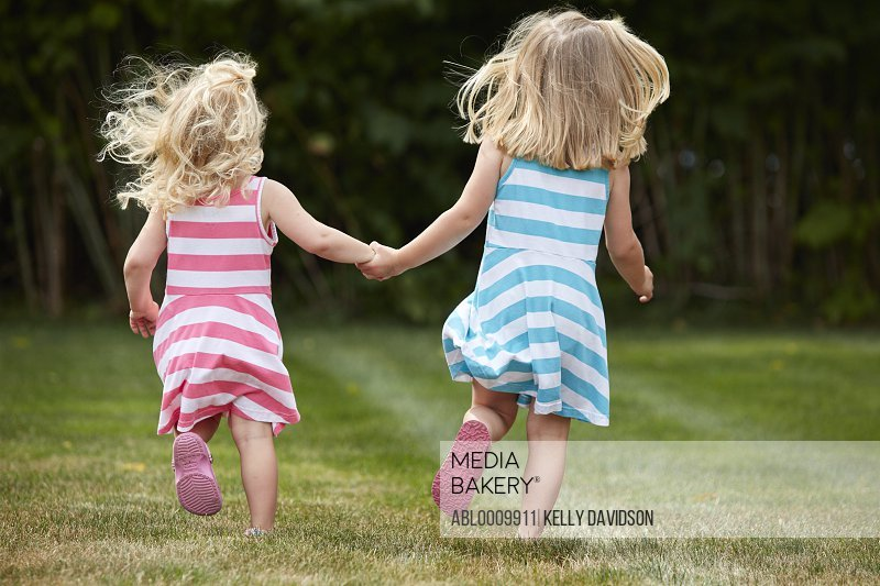 Back View of Two Young Girls Running in Garden Holding Hands