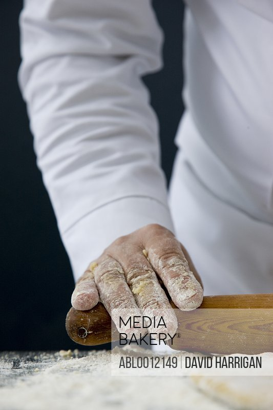 Close up of a chef hand rolling  dough with a wooden rolling pin