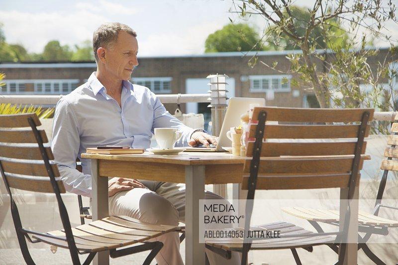 Mature Man Using Laptop at Outdoors Cafe
