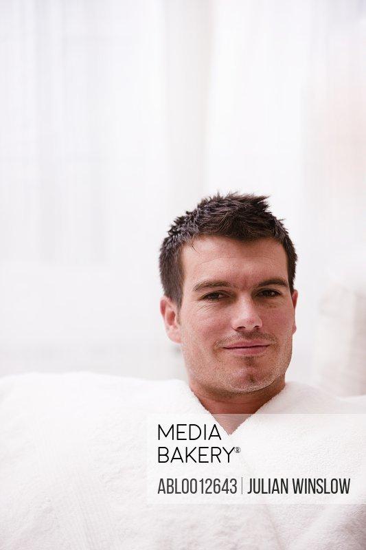 Smiling man in a white bathrobe