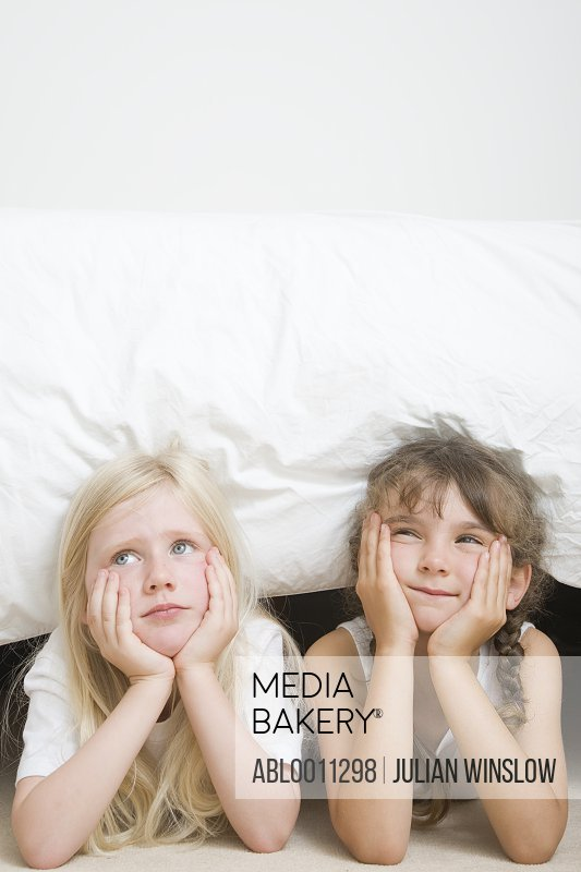 Two young girls with chin resting on hands under bed