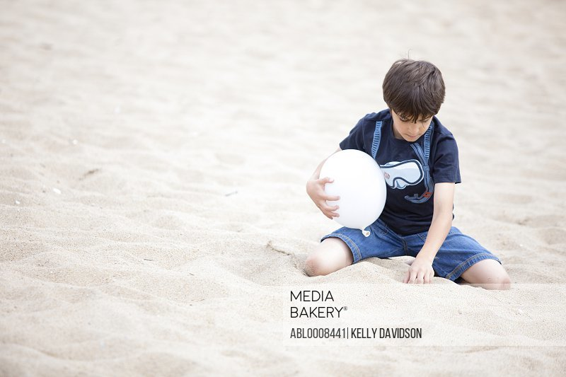 Boy on Beach Playing with Sand
