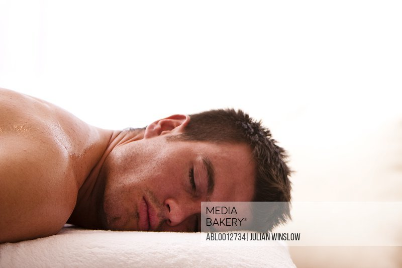 Profile of a man lying on a treatment bench with his eyes closed