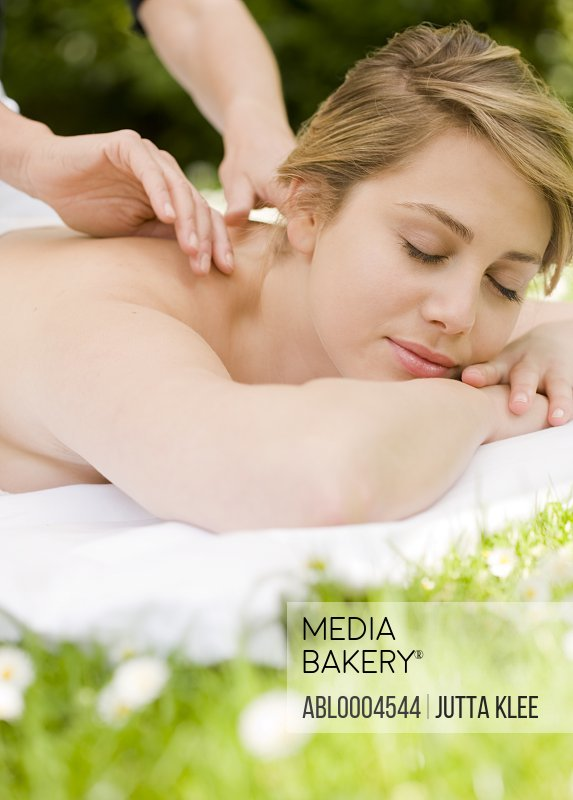 Young woman lying on the grass receiving a massage