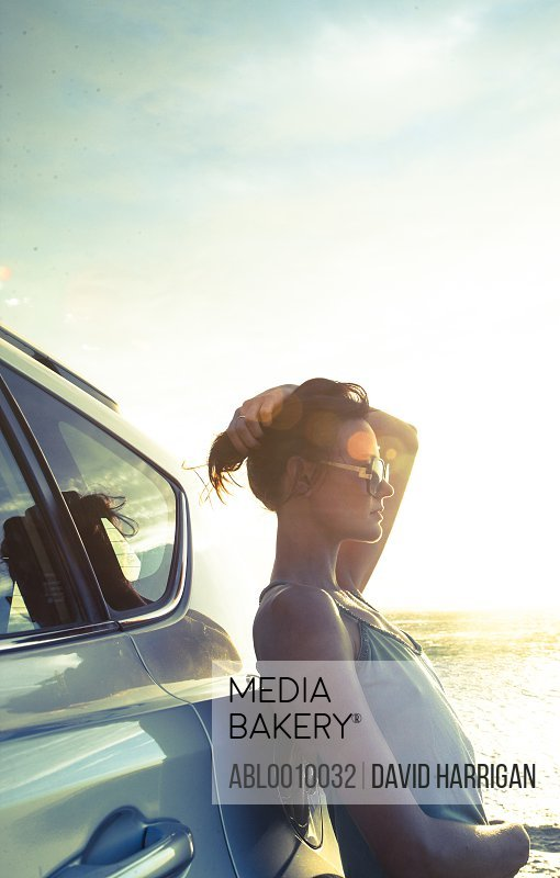 Woman Leaning against Car at Sunset by Ocean
