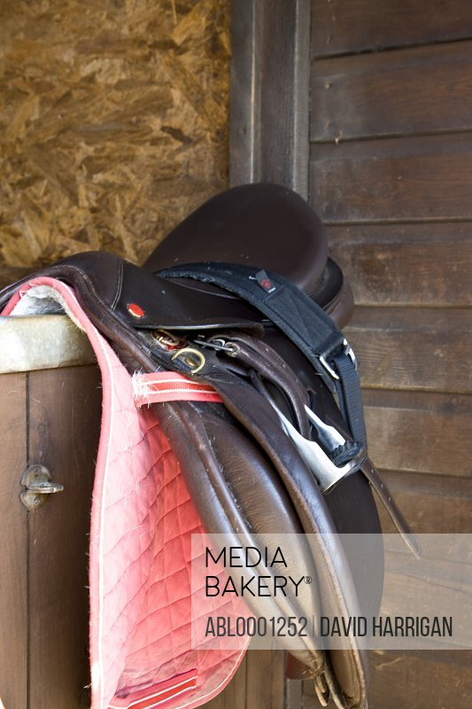 Leather saddle hanging from stable door