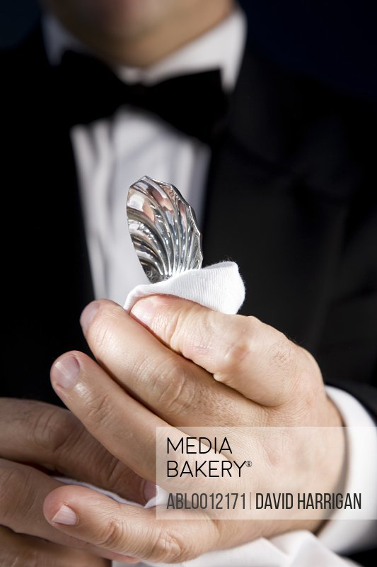 Close up of a waiter polishing a silver spoon with a white napkin