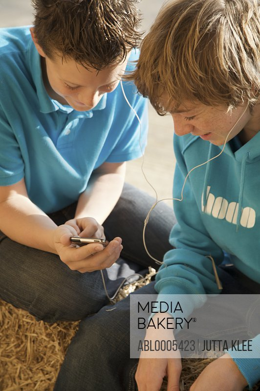 Two teenage boys sitting on a bale of hay sharing an mp3 player