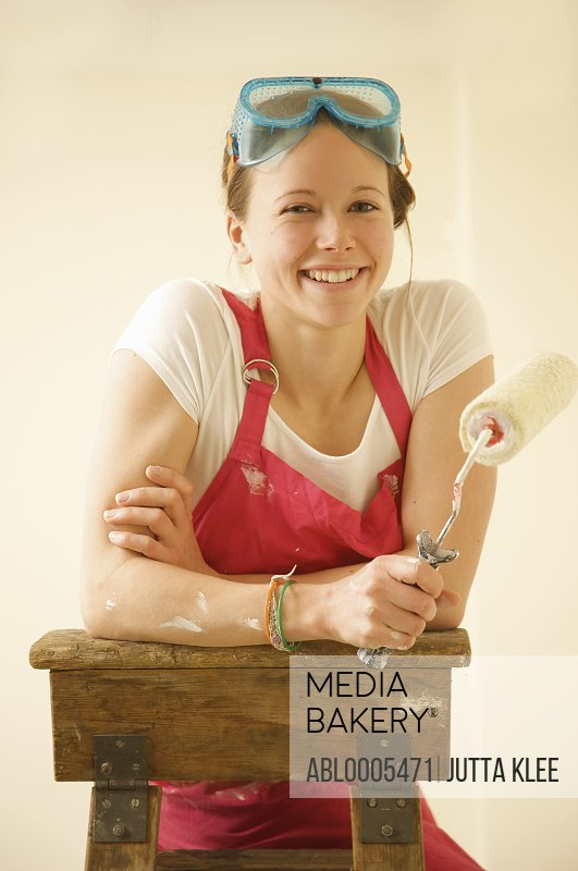 Portrait of a smiling woman standing on a ladder holding a paint roller