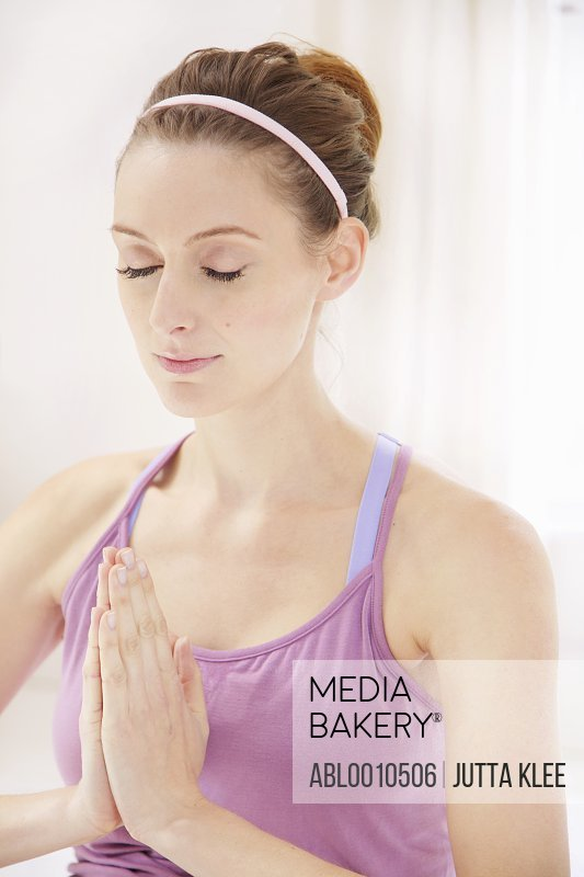 Young Woman Meditating with Hands Together