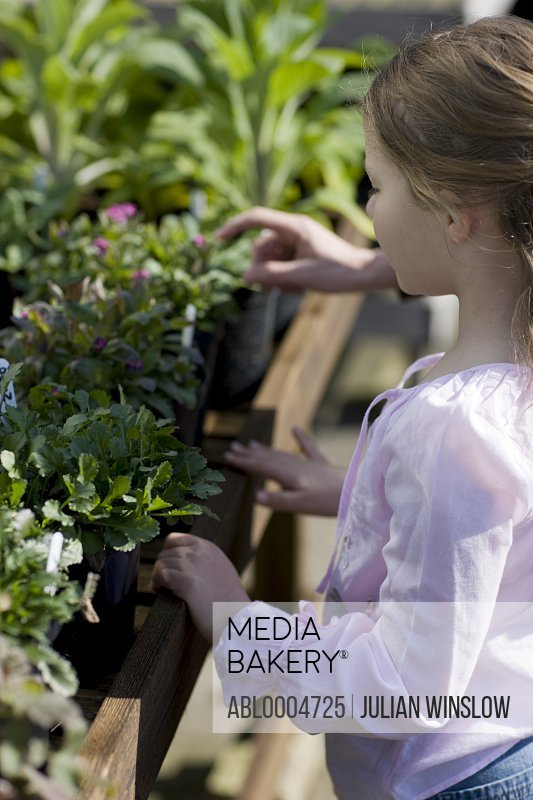 Young girl in a nursery looking at plants