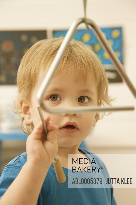 Young boy holding a wand playing with a musical triangle - idiophone