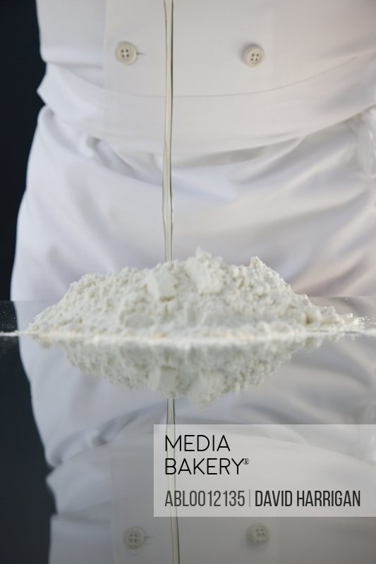 Close up of a chef pouring egg white into a heap of flour  over a glass table