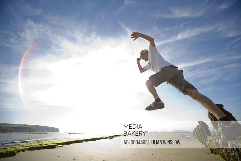 Man in mid air jump on sunny beach