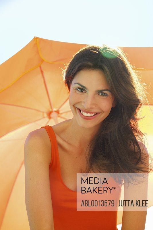 Smiling Woman Under Orange Parasol