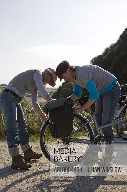 Two women checking bicycle wheel in country road