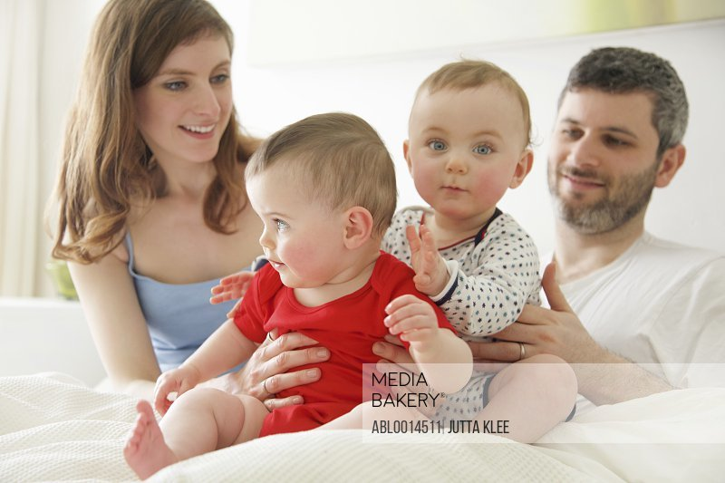 Couple in Bed with Baby Twins