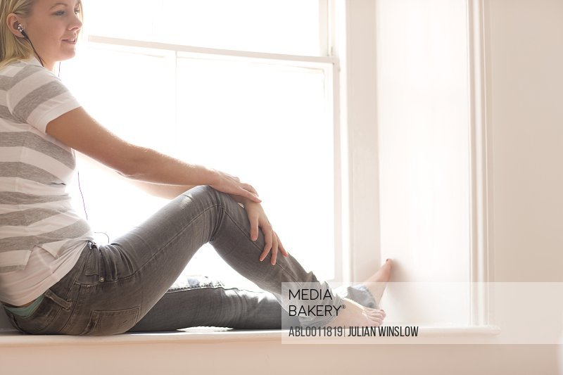 Young woman with earphones sitting on a window sill