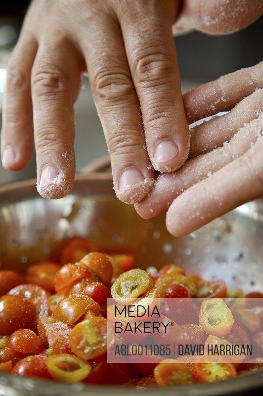 Man's hands seasoning cherry tomatoes with salt