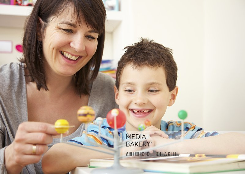 Woman and Young Boy Looking at Solar System Model