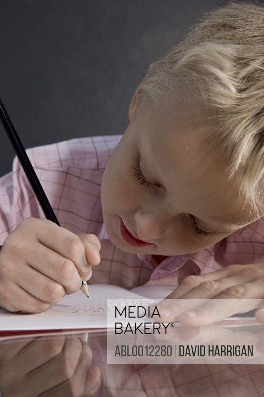Boy sitting at desk writing