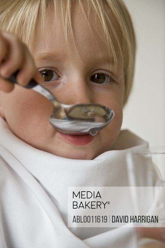 Close up of young blonde boy drinking water with a spoon