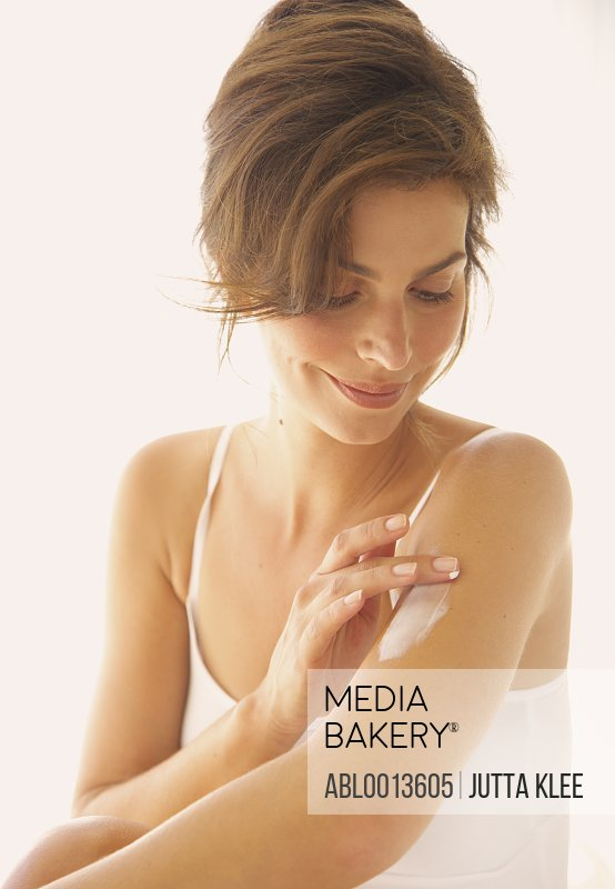 Woman Applying Body Lotion on Arm